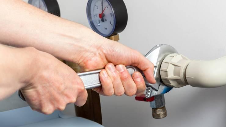 Hands repairing valves in boiler room